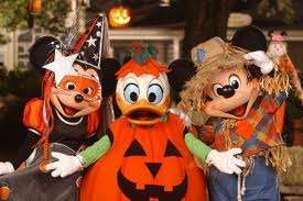 Minnie Mouse dressed up as a witch, Donald Duck as a pumpkin and Scarecrow Mickey